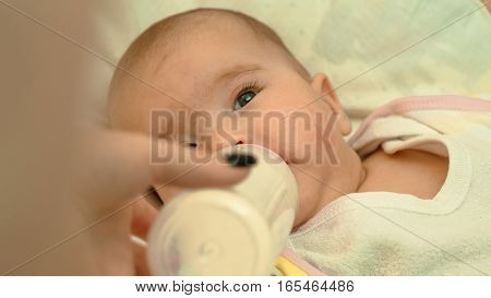 Little newborn baby drinking milk from a bottle close-up