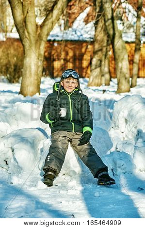 Boy in a winter Park with a Cup in hand
