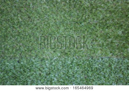 Blurred background of artificial green grass stock photo
