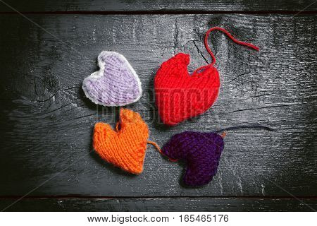 Valentine's Day. Colorful knitted hearts. Red heart on the dark boards. Valentines day. Heart pendant. Red heart. Valentine cards. Space for text. Toning dark colors.