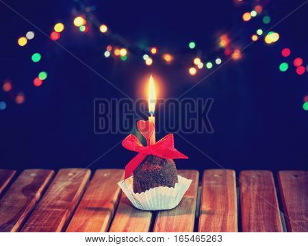 valentine's day chocolate cupcake with candle heart on a wooden table colorful blurred lights dark background