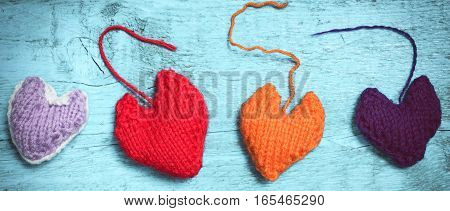 Valentine's Day. Colorful knitted hearts. Red heart on the light blue boards. Valentines day. Heart pendant. Red heart. Valentine cards. Space for text. Letter box look. Toning in bright colors.