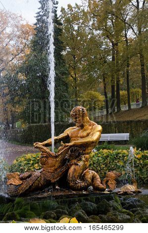 Oranzhereiny Fountain featuring a triton holding open a sea monster's jaws to allow a verticsl column of water to spew forth. Trees with their fall foliage are in the background and mossy rocks in the foreground. Located in Peterhof gardens near St. Peter