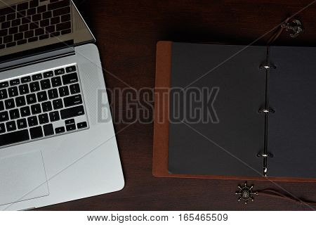 Electronic and paper journal open empty book on wooden table