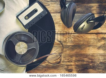 old vinyl record audio cassette tape bobbin and headphones on wooden table retro style toned