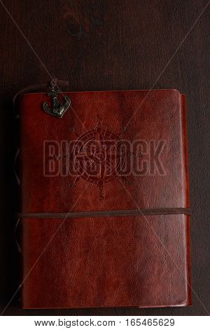 Brown leather closed journal on top of wooden table background. Travel book