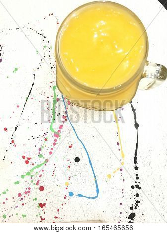 top view mango smoothie in glasses jar on drop color  white table