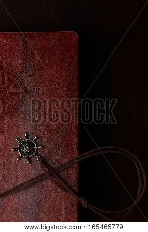 Closeup of half travel diary with brown leather cover on wooden table