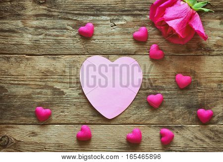 valentine's day one pink rose tag paper many heart scattered on an old wooden table