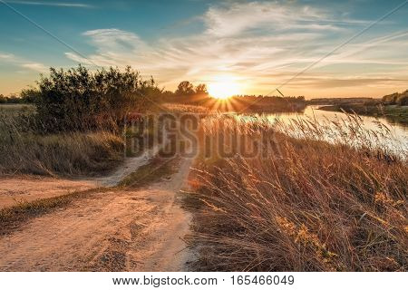 Sunset Over River And Rural Road