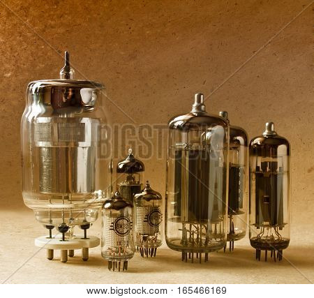 composition of different electronic vacuum tubes on kraft paper background in warm colours