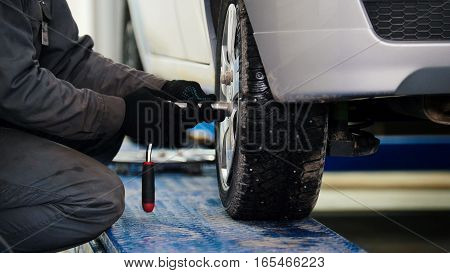 Car mechanic screwing pin car wheel of automobile in service, telephoto
