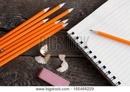 A top view image of several wooden pencils and a open note book.