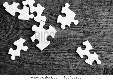 A top view image of several white jigsaw puzzle pieces on a old wooden table.