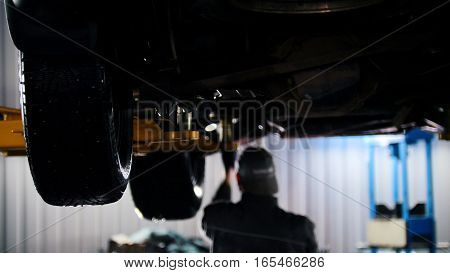 Car service - mechanic unscrewing automobile parts while working under a lifted car, backlight