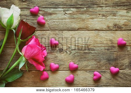 valentine's day three white pink and burgundy roses many scattered heart on an old wooden table