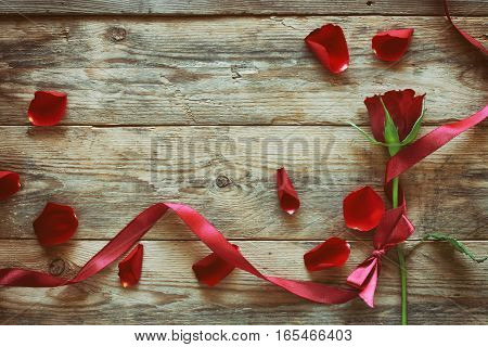 valentine's day red rose silk ribbon scattered petals on the old wooden table