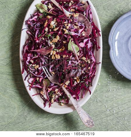Red cabbage beetroot and walnuts salad. Healthy vegetarian detox food. On wooden background top view