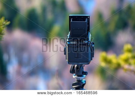 Photo of vintage film camera on tripod on nature background