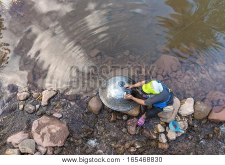 Woman cleaning pan on the side of the river.