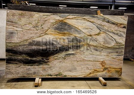 Colorful slab inside marble fabrication workshop - smooth surface sandstone with brownish and gray grains. Background more slabs. Stone, Slab, Counter