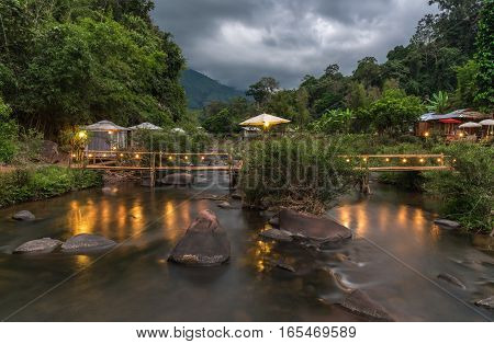 Beautiful waterfront tent and wooden bridge over the river.