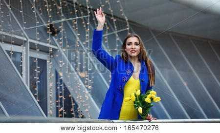 Young attractive girl in a blue coat and yellow dress holding a bouquet of yellow tulips. Spring is coming to town. She welcomes anyone