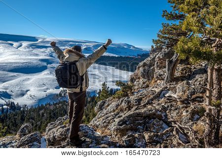 Traveler is standing with raised hands on the edge of abyss above vast forest territory and winter mountains