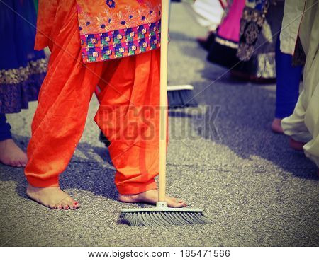 Barefoot Women  With Colorful Clothes Sweep The Asphalt Road Dur