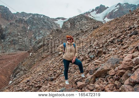 Aged sport woman are standing on the rocks near the snow peak with glacier Tien Shan mountains Almaty Kazakhstan 2016