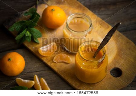 Glass Jars With Natural Baby Food With Tangerine On The Wooden Table