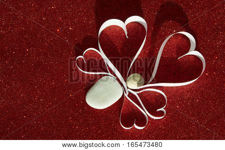 Five white hearts from paper with stones on red shining background
