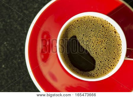 Red and white cup of coffee on black background top view