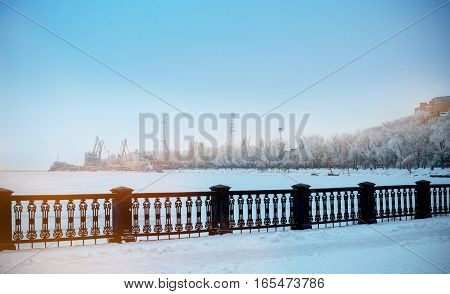 Winter landscape, snow among frosty winter trees. Winter landscape of solid sea 	embankment. Trees in a park covered with snow. Snow-covered quay. Sunset.