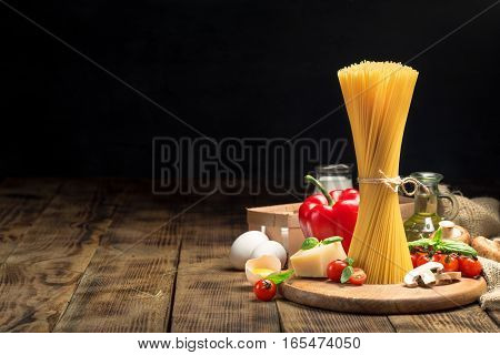 Set raw food for cooking Italian food on a wooden table on a dark background with copy space