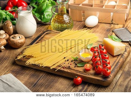 Raw spaghetti with a set of ingredients for cooking Italian pasta on wooden table