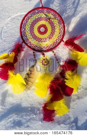 Yellow and red Dreamcatcher made of feathers leather beads and ropes hanging