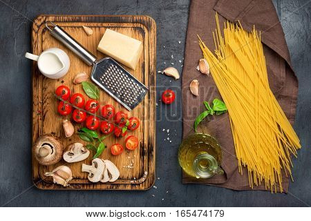 Italian spaghetti with a set of ingredients for cooking pasta on a dark surface top view
