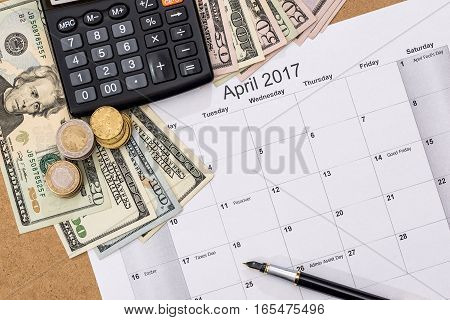 calendar with tax due date and us money pen calculator. April 2017.