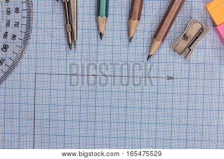 Measuring tools above a blue graph paper.