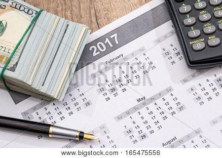 Us Dollars calculator pen and 2017 calendar.