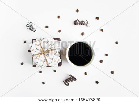 Handmade gifts and a cup with coffee on white background decorated with coffee beans and paper serpentine streamers. Rustic style cute paper DIY decoration. Holiday concept. Flat lay top view