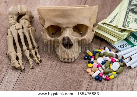 plastic skull of dollars pills drugs and syringes.