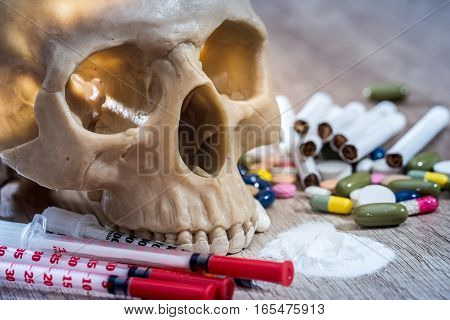 plastic skull with pills drugs and syringes.