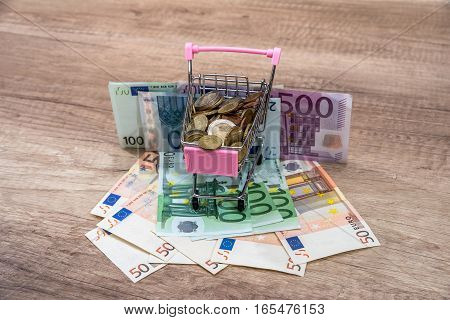 Euro money in a shopping cart on a wooden table