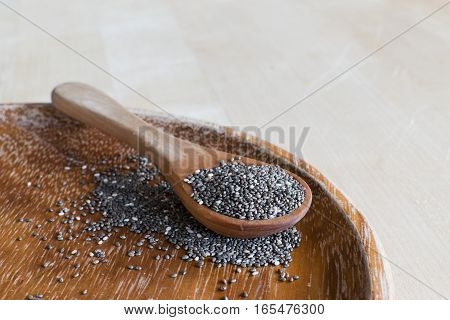 Chia seeds on spoon on wooden background.