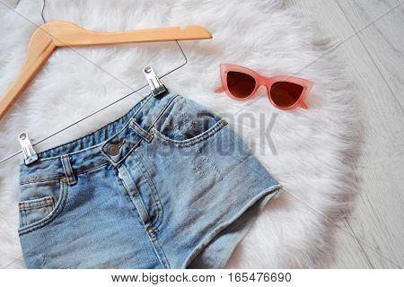Short denim shorts on trempel on white fur and pink glasses. View from above