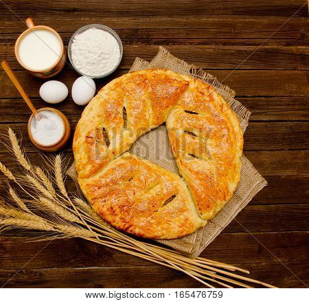 Pie on sacking ingredients for baking wheat ears and a mug of milk on wooden background.