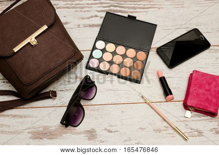 Fashionable concept: eyeshadows handbag glasses lipstick wallet on a wooden background. top view