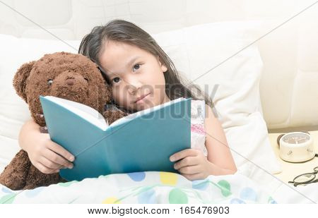 Cute Little Asian Girl In Nightdress Reading A Book With Teddy Bear On Bed.